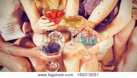 Girls with cocktails toasting against flying colours