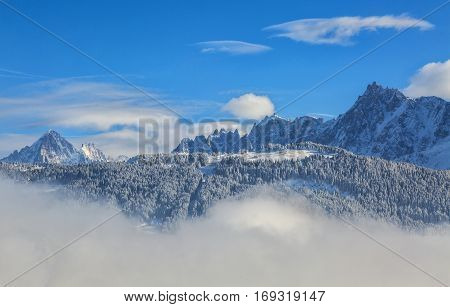 High mountains peaks (Aiguille du Midi 3842m and Aiguille du Plan 3673m) over the clouds in Mont Blanc Massif in the French Alps.
