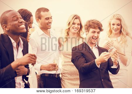Well dressed people looking smartphone on night out