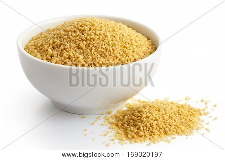 Dry Couscous In White Ceramic Bowl Isolated On White. Spilled Couscous.