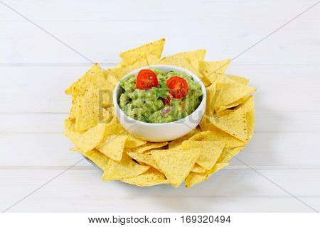 bowl of guacamole with corn tortilla chips on white background