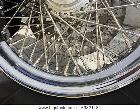 Close up of a motorcycle tyre showing spokes and rubber with space for text.