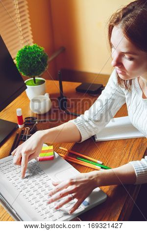 Young business woman working with laptop, sitting at table. Multitasking concept. Telework concept. Work at home