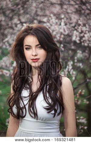 Sensual young woman standing in white dress at blossoming tree in the garden. Beauty of woman and nature consept. Portrait of beautiful model with curly brown hair posing and looking at camera.