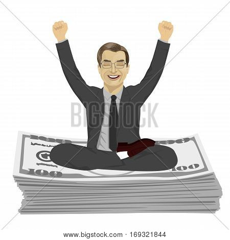 Mature businessman with arms up celebrating his success sitting on dollar bills stack over white background