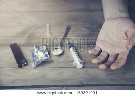 young stoned man with drugs on the table