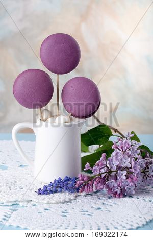 Purple French macaroons cookies and marshmallow on a stick in a vase like a bouquet lilac flowers