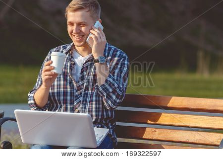 A young male businessman with a laptop and telephone. Remote work outdoors