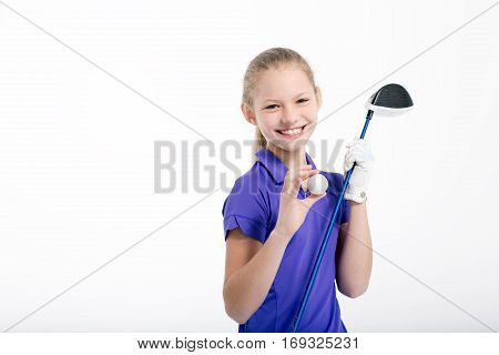 Pretty girl golfer posing with golf club and ball on white backgroud in studio