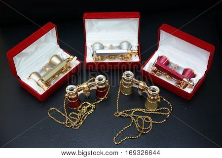 vintage Opera glasses in red boxes on dark background