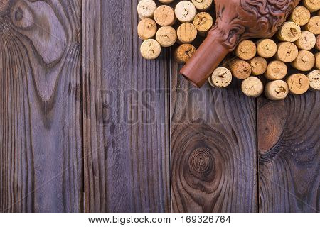 Clay bottle of wine and cork on a dark wooden table