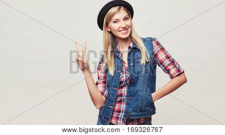 Closeup fashion studio portrait of hipster young smiling woman in black hat and denim vest over light grey background