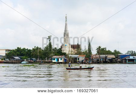 Tien Giang, Vietnam - Nov 28, 2014: Tien river scene in Mekong Delta, with rowing boats and church on background
