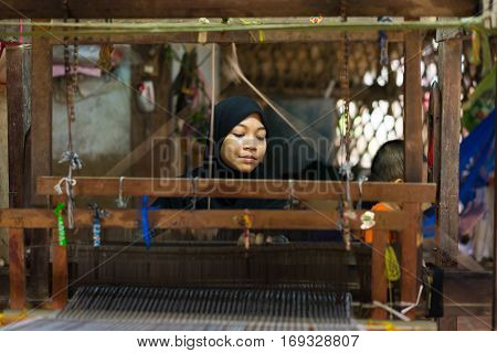 An Giang, Vietnam - Nov 29, 2014: Champa woman weaves textile at home at Cham village, Mekong delta, Vietnam