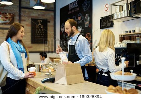 Female guest ordering takeaway in cafeteria.