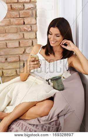 Attractive young woman sitting in cosy bean bag chair, using mobilephone, smiling happy, relaxing.