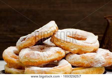 Donuts sprinkled with powdered sugar dark wood background. Close-up side view