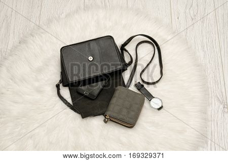 Open black bag with a spill out of her phone a gray purse and a watch. The white fur on background top view. fashion concept
