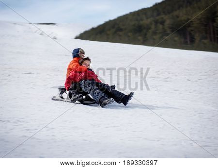 Happy friends in winter sledding from a hill