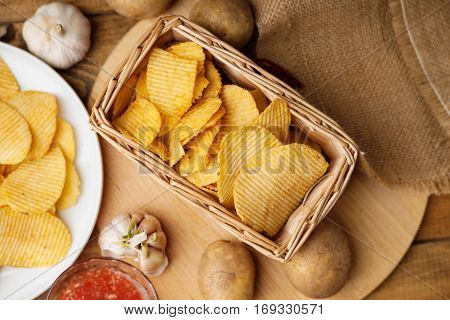 Crispy potato chips in a wicker basket, potato, gralic and sauce