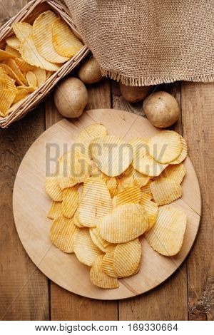 Crispy potato chips and potato on a wooden background