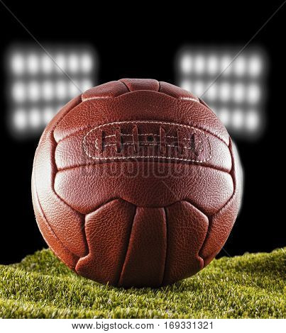 Old football over green grass with stadium lights on the back vertical image