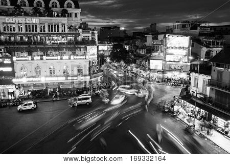 HANOI VIETNAM - AUGUST 2 2016: Car and people traffic trails and lights in the city center. Typical cafes and restaurants. Sunset sky with illuminated buildings. Black and white