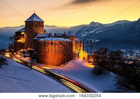 Vaduz Liechtenstein. Illuminated castle of Vaduz at sunset - popular landmark at night with car traffic lights and sunset sky mountains at the background
