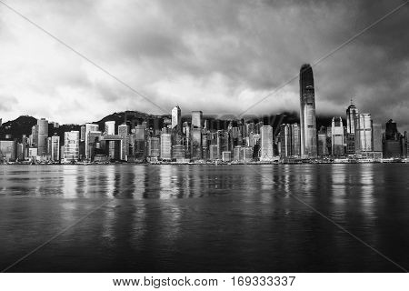Skyline of Hong Kong in the morning. Beautiful skyscrapers with colorful sunrise sky. Black and white