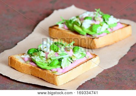 Avocado sandwiches on paper and metal background. Open sandwiches made with white bread, sliced avocado, lettuce, basil and pumpkin seeds. Healthy breakfast recipe
