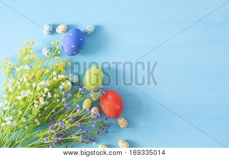 Easter Eggs With Flowers On Blue Table.