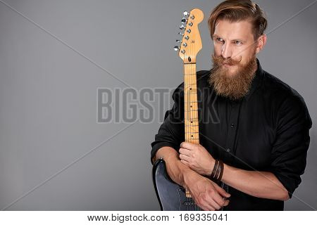 Closeup portrait of hipster man with beard and mustashes wearing black shirt holding guitar looking away, over grey background