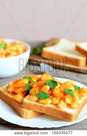 Baked white beans with carrot and parsley on white bread slices. Baked white beans in a bowl, bread slices, spoon on vintage wooden table. Healthy diet idea. Vertical photo
