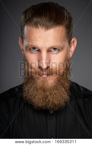Closeup portrait of hipster man with beard and mustashes wearing black shirt gazing at camera