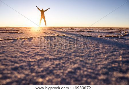 Salar de Uyuni: Male tourist jumping as the sunrise at the salt lake creates a beautiful pattern.