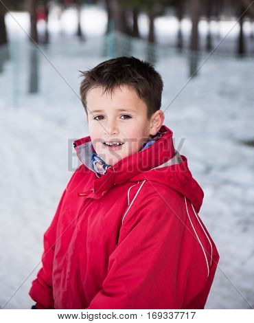 Portrait of a boy in winter close-up looks at the camera