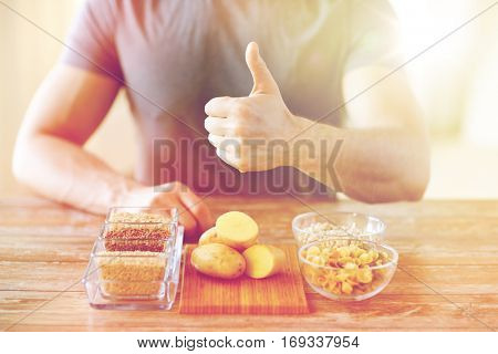 healthy eating, diet, gesture and people concept - close up of male hands showing thumbs up with carbohydrate food on table