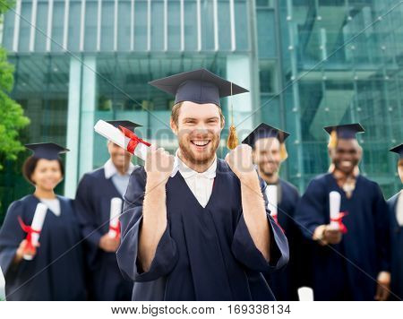 education, gesture and people concept - group of happy international students in mortar boards and bachelor gowns with diplomas celebrating successful graduation over university building background