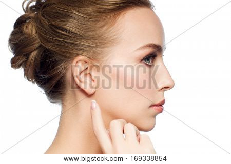 health, people and beauty concept - beautiful young woman pointing finger to her ear over white background