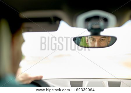 road trip, transport and people concept - rearview mirror reflection of man driving car