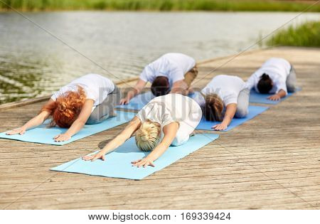 fitness, sport, yoga and healthy lifestyle concept - group of people making childs pose on river or lake berth