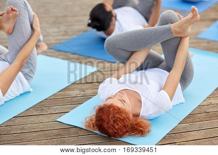 fitness, sport, yoga and healthy lifestyle concept - group of people making half ankle to knee supine pose on river or lake berth