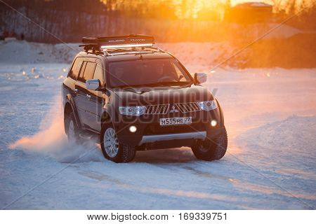KHABAROVSK RUSSIA - JANUARY 28 2017: Mitsubishi Pajero Sport moving on ice of a frosn river at sunset