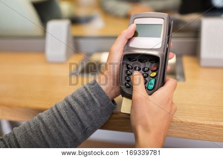 finance, money, technology, payment and people concept - hand entering pin code to card reader terminal