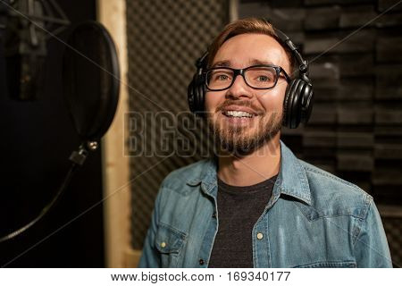 music, show business, people and voice concept - male singer with headphones and microphone singing song at sound recording studio