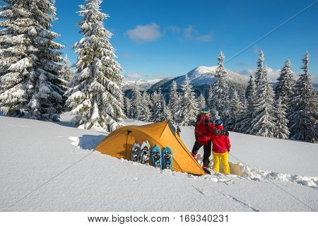 Couple of travelers relax near a tent and equipment in the mountains in winter at sunny magic day after snow storm - winter adventure. Back view.