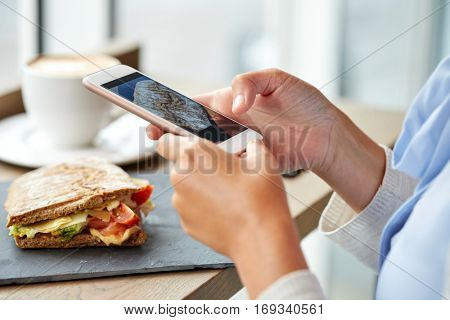 food, culinary, technology and people concept - woman hands with smartphone photographing panini sandwich at restaurant