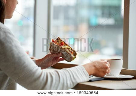 food, dinner and people concept - woman eating salmon panini sandwich with tomatoes and cheese and drinking coffee for lunch at restaurant