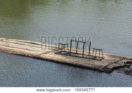 Bamboo rafts floating in the river and dining table and chair