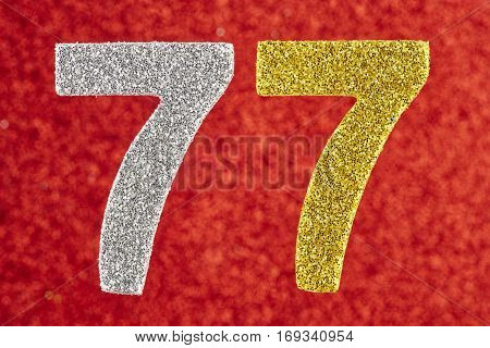 Number seventy-seven yellow silver color over a red background. Anniversary. Birthday